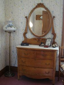 Antique oak dresser adorned with antique baby shoes